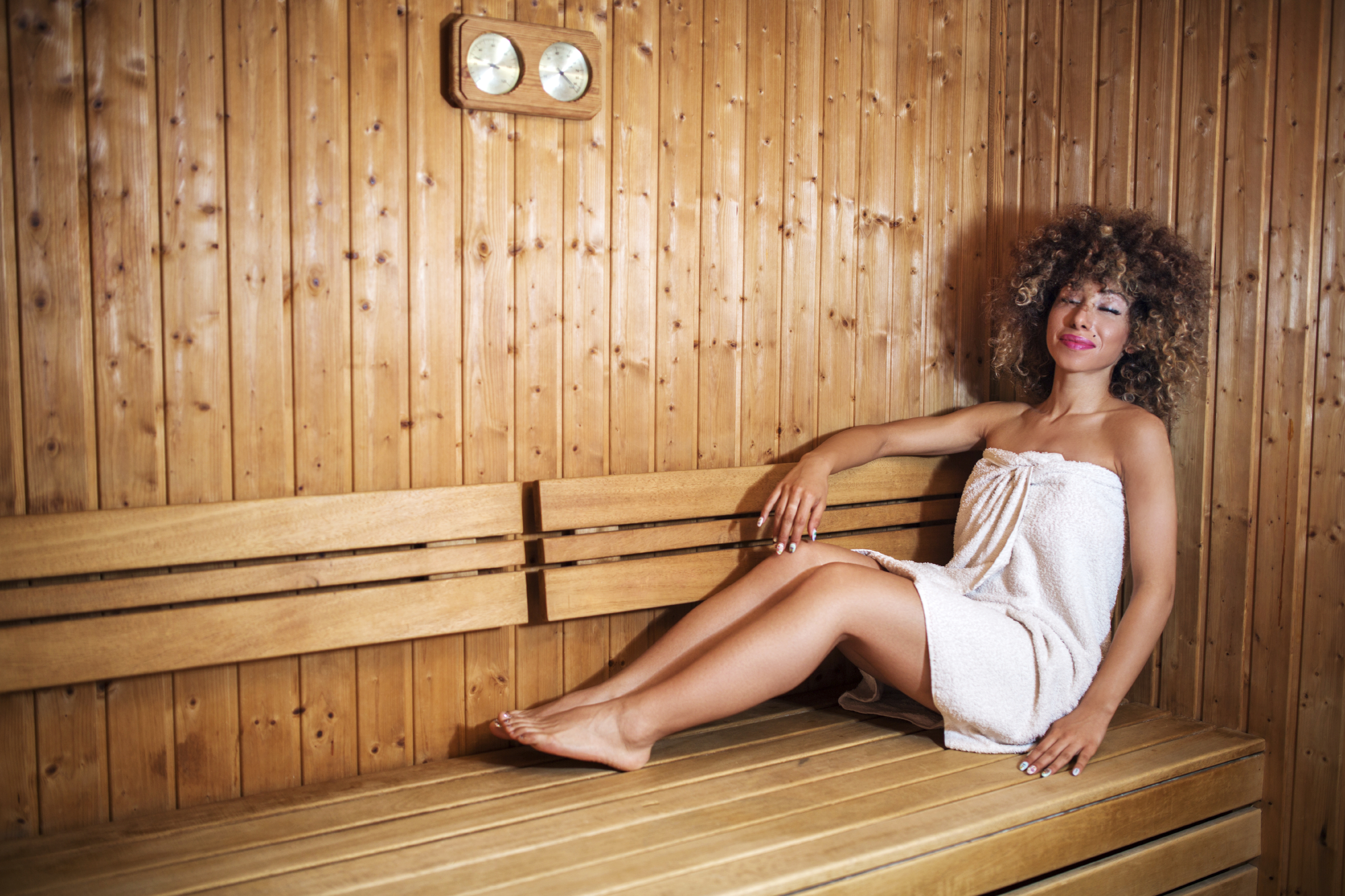Smiling African American woman enjoying in sauna.